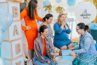 Female friends open gift boxes with a pregnant woman at a baby shower
