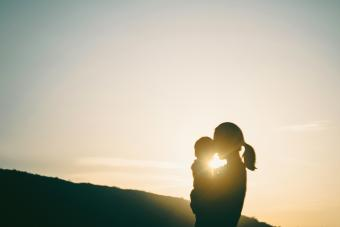 Silhouette of mother carrying baby girl outdoors against sky