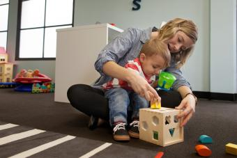 Baby sitter and boy playing with geometric puzzle box