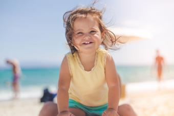 toddler girl smiling at the beach