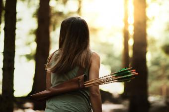 young girl in woods with bow and arrow