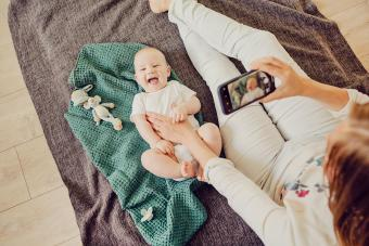 Mother photographing her baby using mobile phone