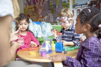 Children doing science experiment at table in preschool