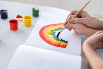 Hands of a child in the hands of an adult learn to draw a rainbow