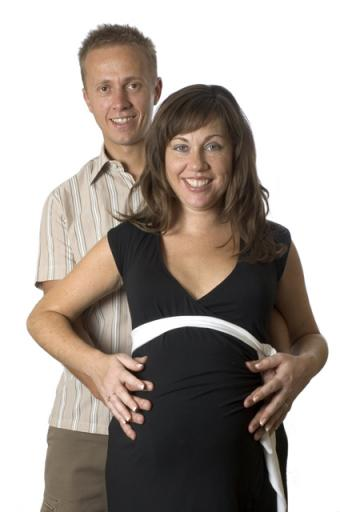 Couple both holding wife's pregnant belly