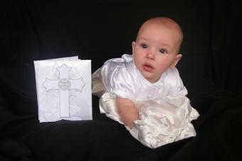 Baby in baptism gown with baptism book