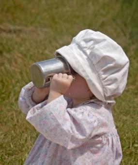 Baby girl drinking from a tin mug
