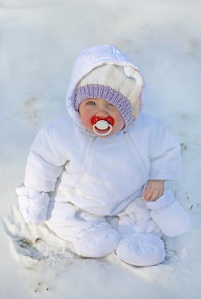 Infant wearing a one-piece snowsuit