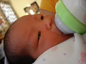 Newborn baby being bottle fed