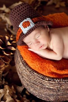 Newborn baby wearing a Thanksgiving pilgrim hat
