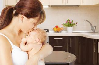 Mother and baby listening to water running in kitchen
