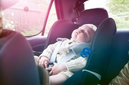 Boy sleeps in baby car seat