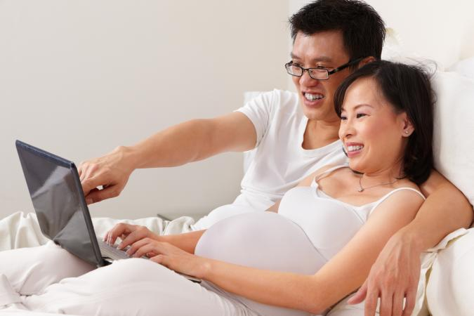 couple smiling in front of pc