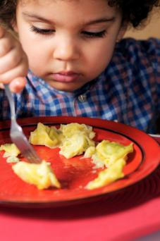 Kid eating pasta