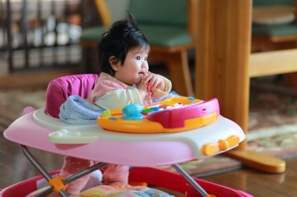 baby sitting on a walker