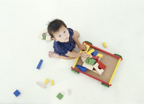 boy putting blocks in wagon