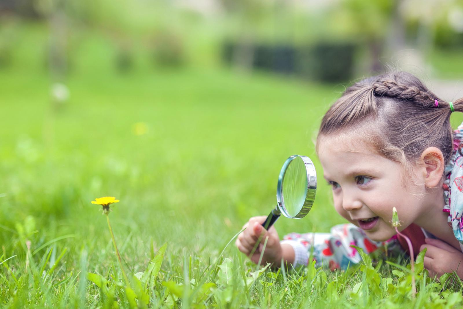 Girl with magnifying glass examining flower
