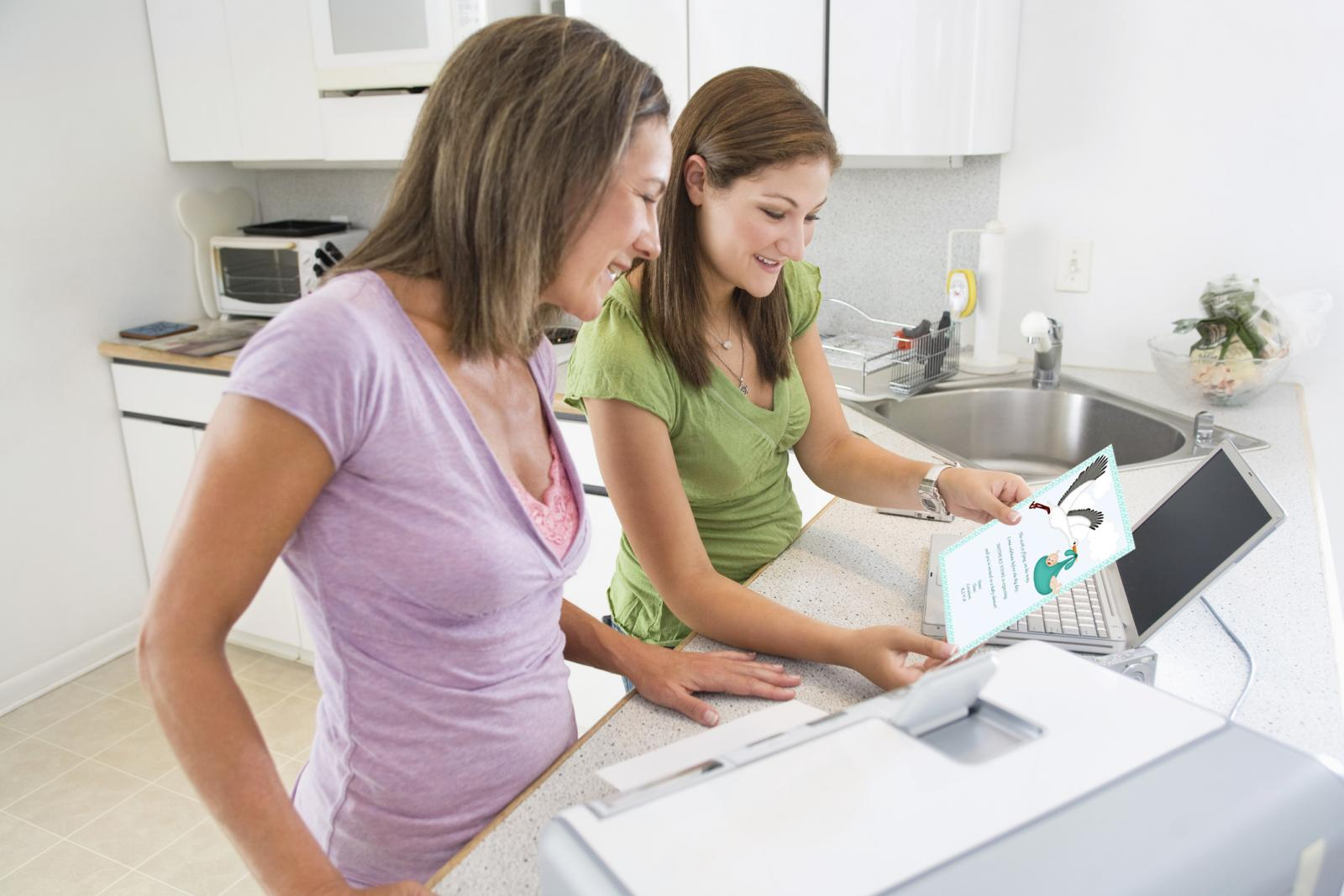 Mother and daughter using computer and printer