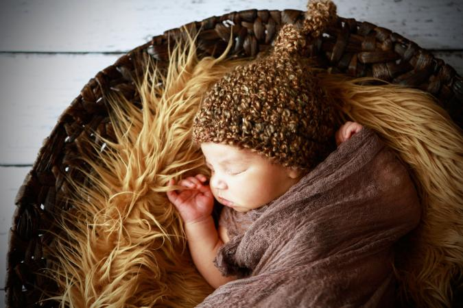 Newborn sleeping in fur lined basket