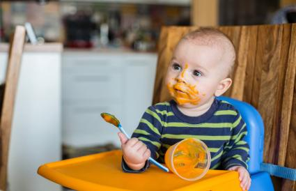 Baby boy eating mashed food