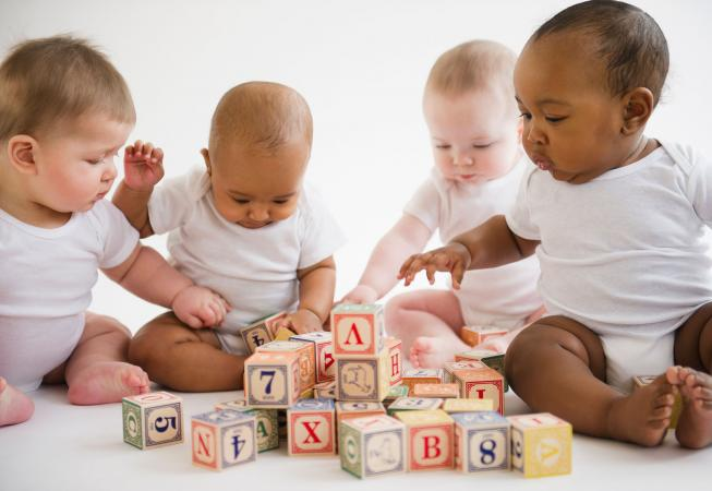 Four babies playing with blocks