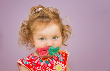 Toddler girl with two pacifiers