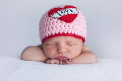newborn baby wearing love hat