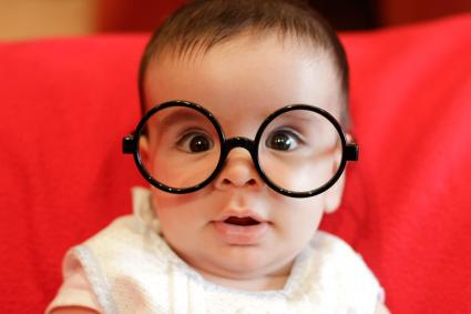 Closeup of baby wearing black glasses