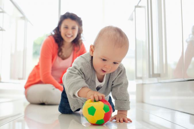 Baby crawling toward colorful ball