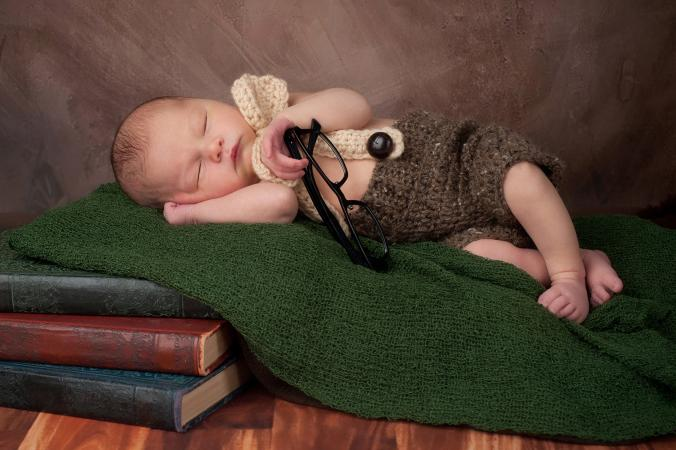 Baby sleeping on literature books