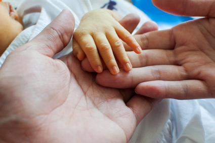 A close up shot of father and baby's hand with yellow skin