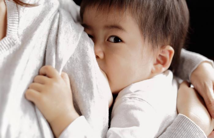 Baby boy being breastfeeding fed