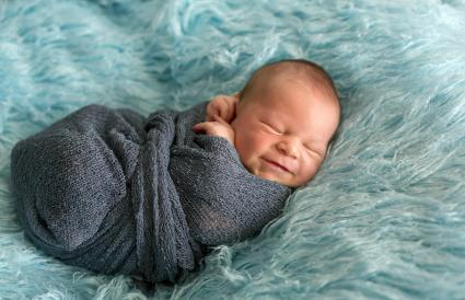 Happy smiling newborn baby in wrap