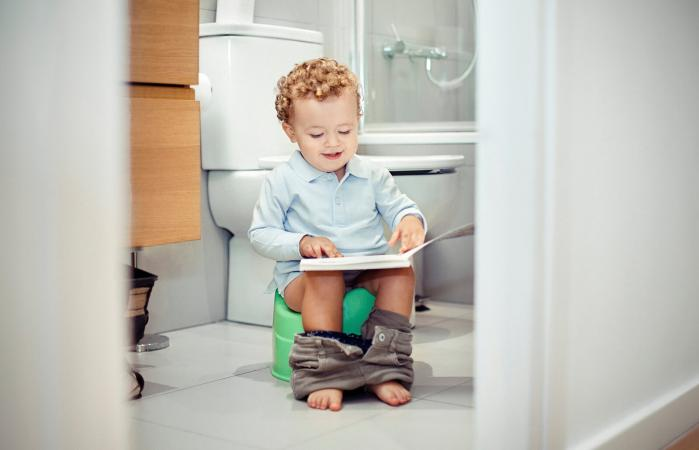 Child sitting on potty chair