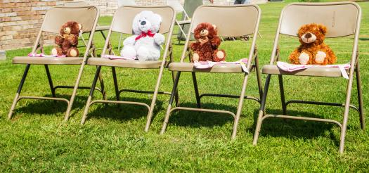 Four seated Teddy Bears lined up at a baby shower
