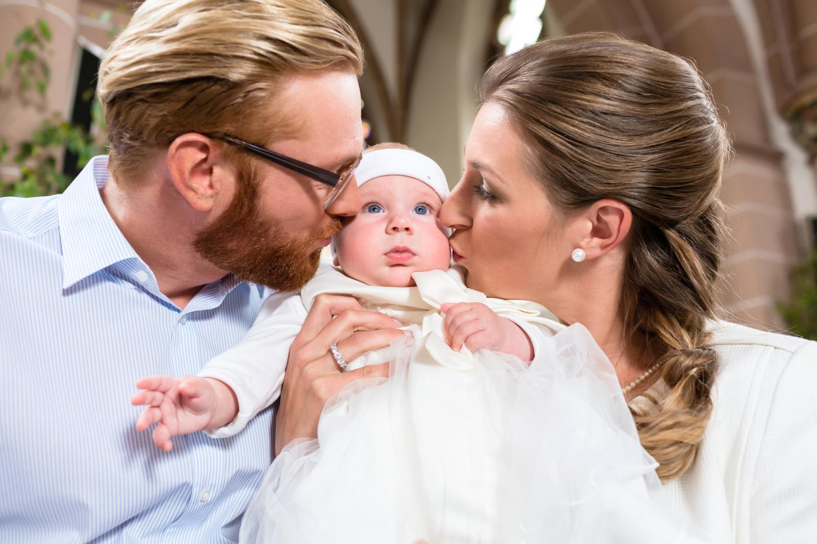 Godparents kissing baby at christening