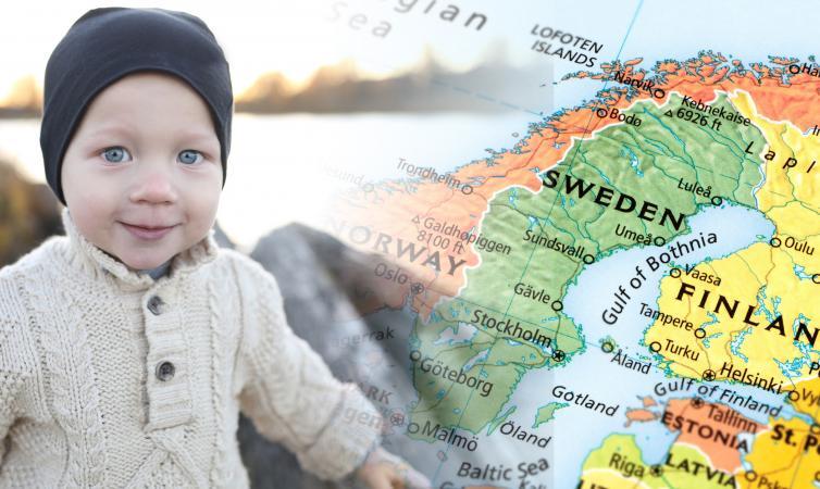 Smiling boy at lake with Scandinavian map