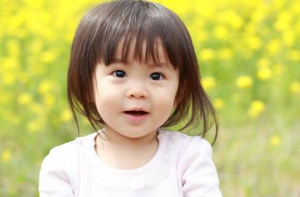Japanese baby girl sitting in yellow field mustard