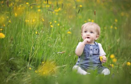 baby sitting in flowery meadow