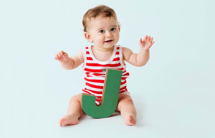 Baby boy playing with cardboard letter J