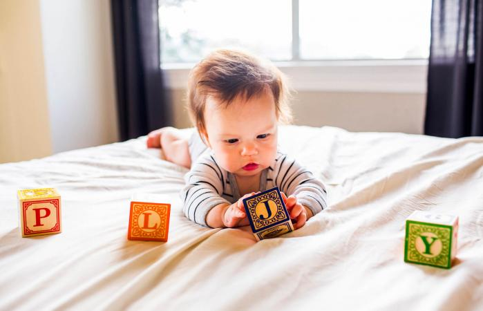 baby girl playing with blocks on bed