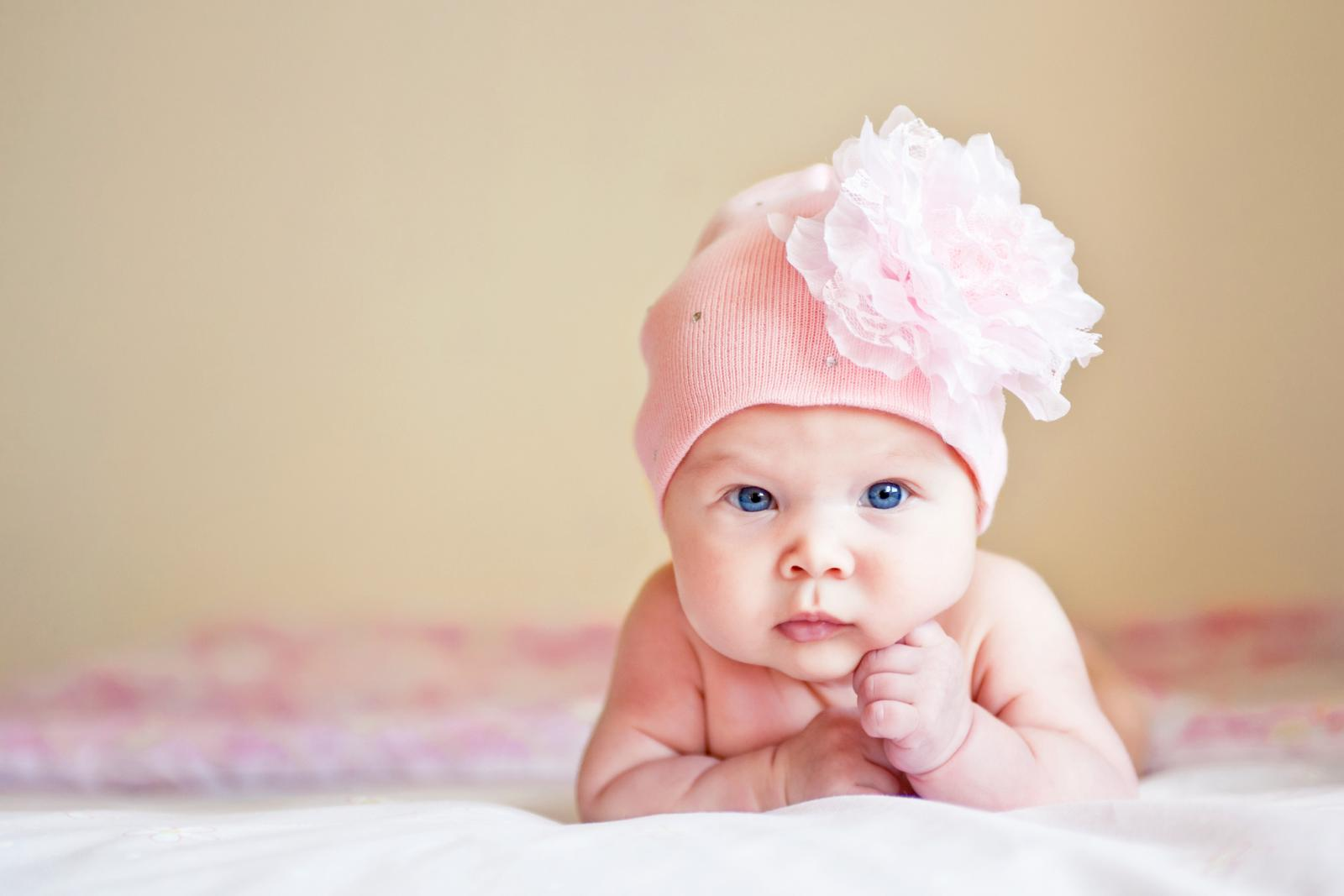 Model baby in hat with flower