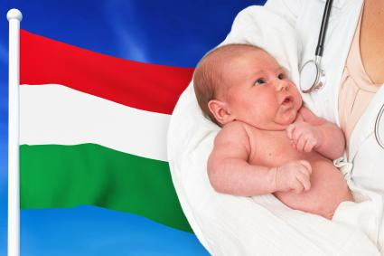 Newborn baby in hands of doctor with Hungary national flag