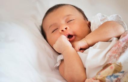 newborn baby sleeping on bed
