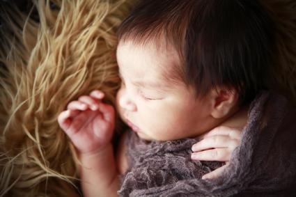 Newborn Sleeping on Fur Rug
