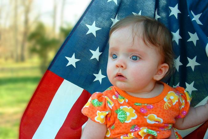 Baby girl sitting in front of an American Flag