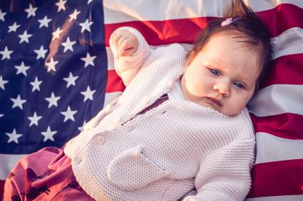 Baby lying on US flag on the grass in nature