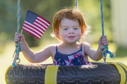 Two year old red-headed girl holding American flag