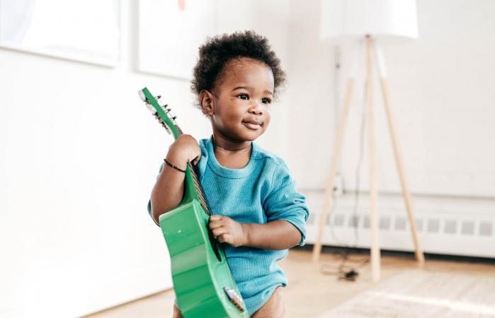 Toddler holding guitar