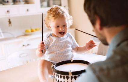 Father with little boy playing drum